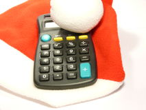 Calculator and Santa cap. Calculator lying on Santa hat over white Royalty Free Stock Image