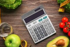 Calculator and set of healthy food. On wooden table Royalty Free Stock Photos