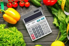Calculator and set of healthy food. On wooden table Royalty Free Stock Photography
