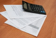 Calculator with sheets of paper. On a light wooden background Stock Photo