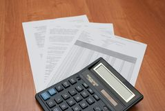 Calculator with sheets of paper. On a light wooden background Royalty Free Stock Photography