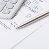 Calculator with silver pen and utility bill under it - close up shot Stock Photos