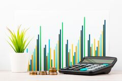 Free Calculator, Stack Of Coins In Front Of Desk With Business Charts And Graphs. Business Planning,accounting,analysis,financial Royalty Free Stock Image - 198044616