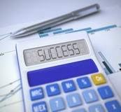 Calculator with success result. Close-up of a calculator with success text written on it and a chromed pen on a financial chart sheet Royalty Free Stock Photo
