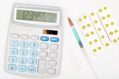 Calculator, syringe and pills on grey background Stock Photography