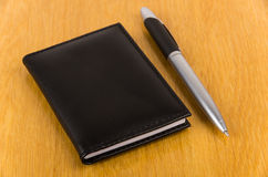Notepad and pen on table Stock Photos