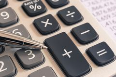 Calculator for tax accounting services, vintage filter. Closeup the silver modern pen on calculator and summary financial statement in background, vintage stock photography