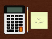 Calculator with tax return note lying on desk Royalty Free Stock Photo