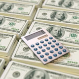 Calculator on top of dollar bills Stock Photography