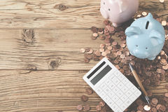 Calculator with two piggy banks and coins. Viewed from above on a wooden table with copy space in a financial, savings, investment, costs and planning concept Royalty Free Stock Photos