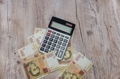 Calculator and ukrainian hryvnia on wooden table royalty free stock photo