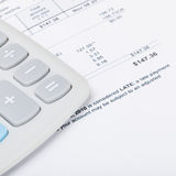 Calculator with utility bill under it - close up studio shot Royalty Free Stock Photos