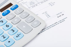 Calculator with utility bill under it Stock Photo