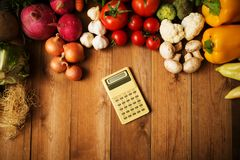 Calculator with vegetables on a Wooden Background.  Stock Photo