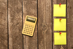 Calculator and yellow blank adhesive note on wooden background Royalty Free Stock Photo