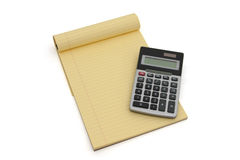 Calculator and yellow lined notepad Royalty Free Stock Image