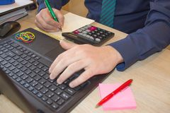 The calculators, business owners, accounting and technology, business, computer, laptop, calculator and documents in the office. Business male hands in office Stock Image