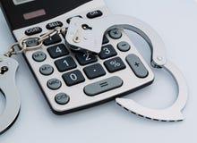 Calculators en handcuffs stock foto's