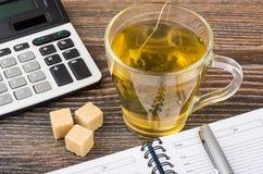 Calculatrice électronique, tasse de thé et carnet Photographie stock libre de droits