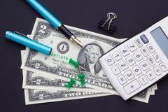 Calculatrice, argent et stylo-plume sur un fond noir photo stock