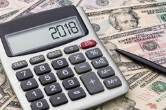 Calculatrice avec l'argent - 2018 Photographie stock