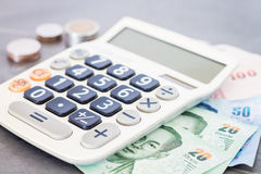 Calculatrice avec l'argent sur le fond gris Photographie stock libre de droits