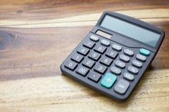 Calculatrice avec le fond en bois de table Photographie stock libre de droits