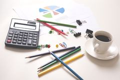 Calculatrice avec les crayons et le café colorés sur le bureau photos stock
