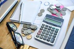 Calculatrice, carnet, stylo, pièces de monnaie sur son bureau photos libres de droits