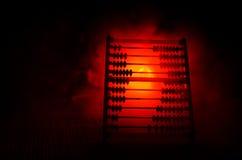 Calculatrice chinoise avec les perles colorées sur le fond orange d'obscurité de fumée du feu Photo de concept des affaires, enfa Photographie stock libre de droits