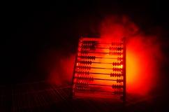 Calculatrice chinoise avec les perles colorées sur le fond orange d'obscurité de fumée du feu Photo de concept des affaires, enfa Photographie stock