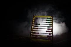 Calculatrice chinoise avec les perles colorées sur le fond orange d'obscurité de fumée du feu Photo de concept des affaires, enfa Image stock