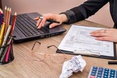 calculatrice d'utilisation de femme avec l'ordinateur portable pour remplir impôt 1040 Photos stock
