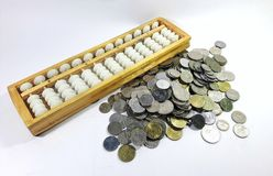 Calculatrice de boulier chinois avec des pièces de monnaie d'argent Photo stock