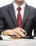 Calculatrice de Calculating Finance With d'homme d'affaires au bureau au-dessus du fond blanc Images libres de droits