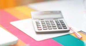 Calculatrice de foyer sélectif et stylo rose à coté sur la souris d'ordinateur Photos stock