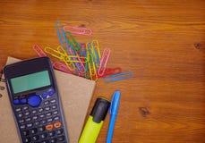 Calculatrice de vue supérieure sur le carnet et la papeterie sur le fond en bois brun Photo stock