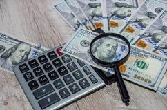 Calculatrice, dollars américains et loupe sur une table en bois photos libres de droits