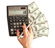 Calculatrice et argent chez des mains de la femme Photo stock