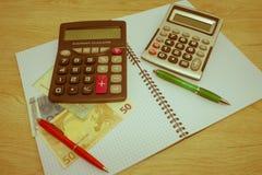 Calculatrice et argent sur la table en bois Le concept de la planification financière, l'épargne Photos stock