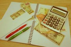 Calculatrice et argent sur la table en bois Le concept de la planification financière, l'épargne Image libre de droits