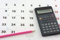 Calculatrice et crayon sur le calendrier Image stock