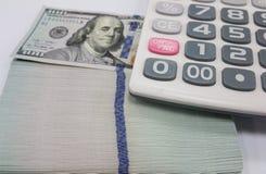 Calculatrice et 100 dollars Image stock