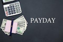 Calculatrice et dollars avec le JOUR DE PAIE de message images stock