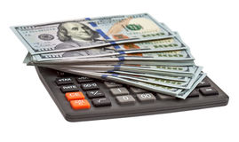 Calculatrice et dollars sur le fond blanc Photographie stock libre de droits
