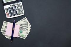 Calculatrice et dollars sur le fond noir Photos stock