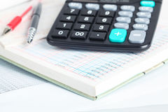 Calculatrice et livres financiers Photos stock