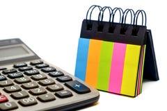 Calculatrice et note collante de papier colorée sur le fond blanc Photo stock
