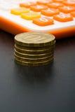 Calculatrice et pièces de monnaie Photographie stock libre de droits