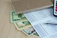 Calculatrice et stylo sur le carnet de compte bancaire avec le billet de banque du dollar Images stock